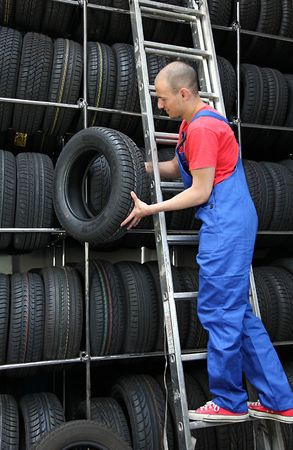 stocktaking: A motivated worker in a tire workshop restocking the goods.