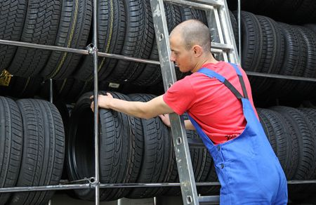 stocktaking: A motivated worker in a tire workshop standing on a ladder and checking the stock.