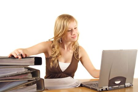 zealous: A young ambitious woman in front of her notebook computer. All isolated on white background.