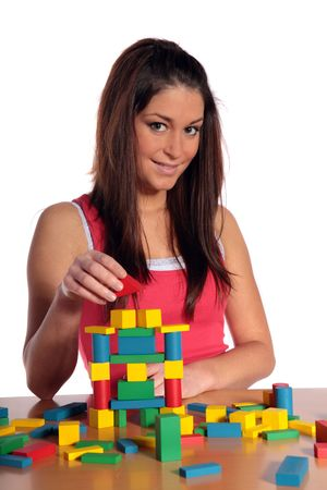 An attractive young woman plays with building bricks. All isolated on white background. photo