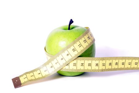metaphorical: A metaphorical image showing an apple measured with a tape showing healthy diet on a white background. Stock Photo