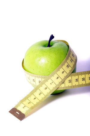 A metaphorical image showing an apple measured with a tape showing healthy diet on a white background. photo