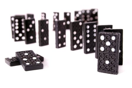 wonky: Several dominoes standing one after another in front o a white background.