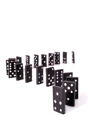 Several dominoes standing one after another in front o a white background. photo