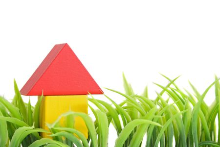 A stylized house out of blocks between blades of grass. All isolated on white background. Stock Photo - 6578397