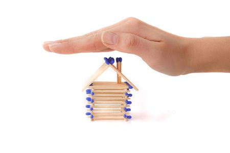 fend: Una mano umana proteggere una casa stilizzata di fiammiferi. Tutti isolati su sfondo bianco.  Archivio Fotografico