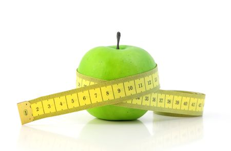 shorten: A fine green apple with a measuring tape symbolizing diet. All on white background. Stock Photo