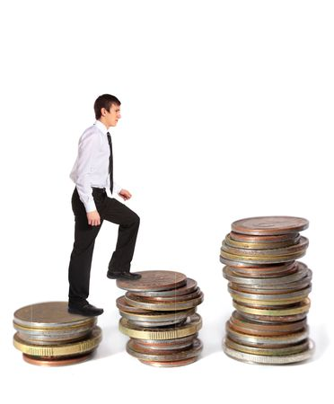 pay raise: A young businessman walking up several pile of coins. All on white background. Stock Photo
