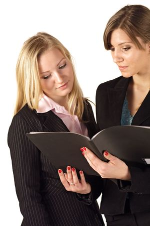 reviewing documents: Two young business women reviewing documents. All isolated on white background. Stock Photo