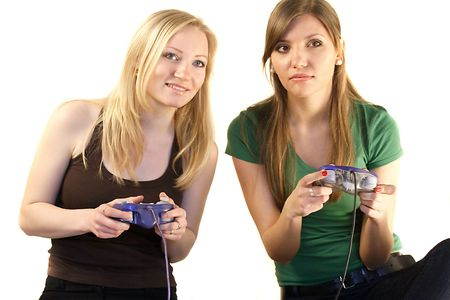 Two young girls playing video games.