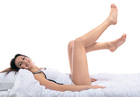 An awake young woman lying on her bed. All on white background. Stock Photo - 6601800
