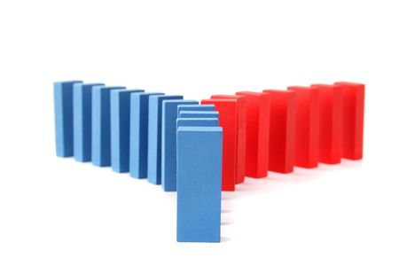 interdependence: A line of blue dominoes with a turning of red ones. All ioslated on white background.