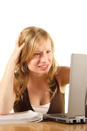 A stressed student in front of her notebook computer. All isolated on white background. photo