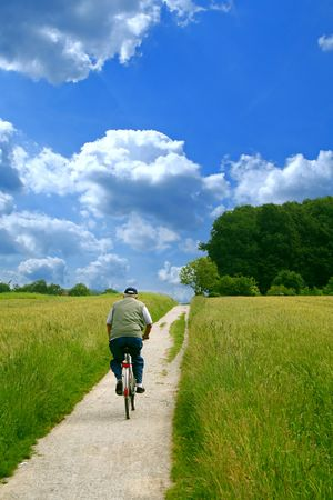 A senior person cycling on a small path. photo