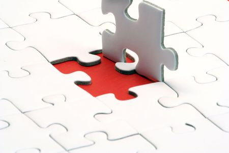 in need of space: A typical jigsaw puzzle with a red gap. Stock Photo