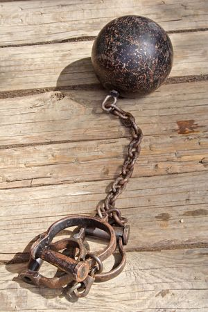 ball and chain: An iron chain from the middle-ages lying on planks.