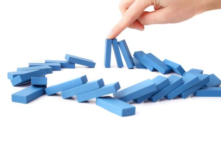hindering: A human hand intervenes a chain reaction of a domino game. All isolated on white background.
