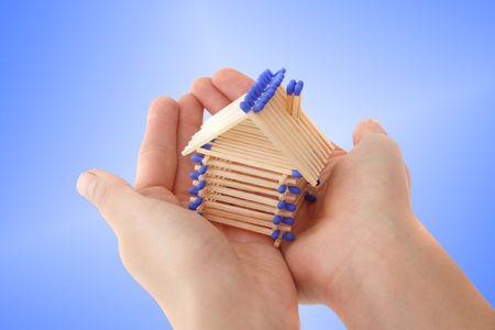 fend: Una mano umana proteggere una casa stilizzata di fiammiferi. Tutto isolato su sfondo azzurro.