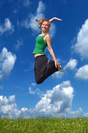 jocularity: A young attractive woman jumping on a meadow in front of a bright blue sky.