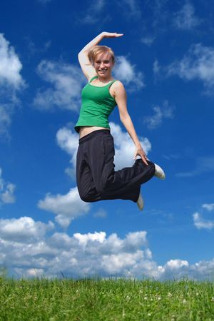 hilarity: A young attractive woman jumping on a meadow in front of a bright blue sky.
