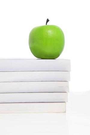 Una manzana verde se encuentra en un montón de libros, simbolizando los estudios. Todo sobre fondo blanco.  Foto de archivo - 6947224