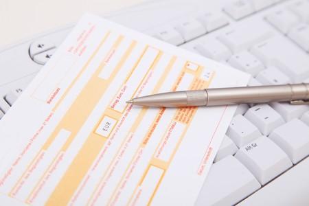 bank overschrijving: Bank transfer form lying on a standard computer keyboard