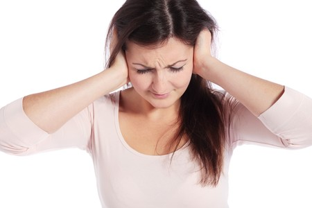 loudness: Attractive young woman suffering from tinnitus. All on white background.