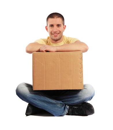 Attractive young man holding moving box. All on white background. photo