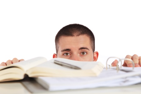 Attractive young man looking behind his study documents. All isolated on white background. Stock Photo - 8488220