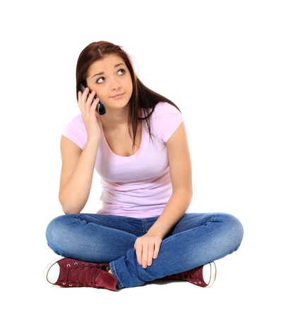 indian style sitting: Attractive teenage girl waiting during a phone call. All on white background.