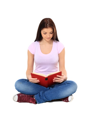 indian style sitting: Attractive teenage girl reading a book. All on white background.