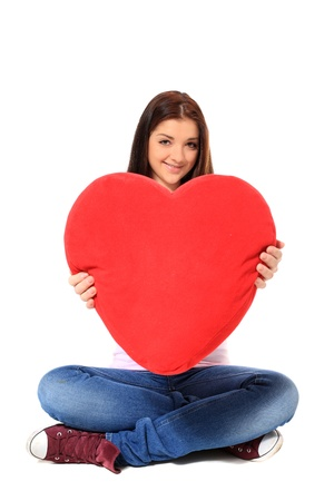 indian style sitting: Attractive teenage girl holding heart-shaped red pillow. All on white background.