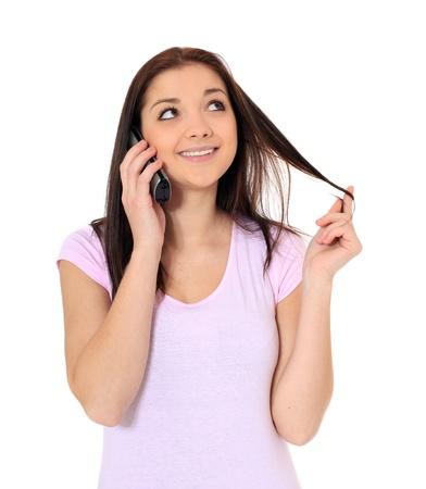 Attractive teenage girl talking on the phone. All on white background. Stock Photo - 8680640