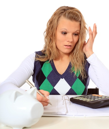 Attractive woman is shocked while doing her budgeting. All on white background.  photo