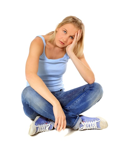 indian style sitting: Frustrated scandinavian girl sitting on floor. All on white background.