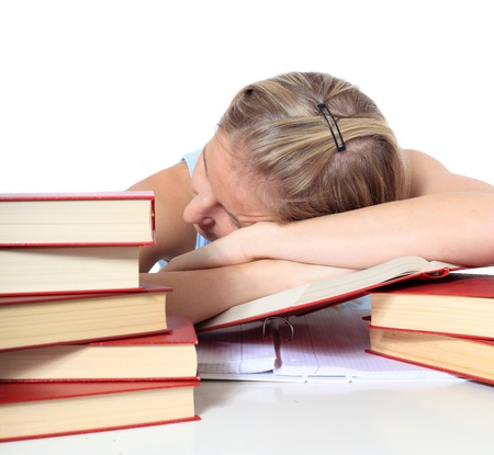 Attractive young scandinavian woman is taking a nap on her study documents. All on white background.  photo
