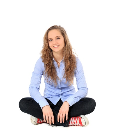 indian style sitting: Attractive young girl sitting on the floor. All on white background.