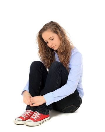 pubertad: Triste ni�a sentada en el suelo. Todo sobre fondo blanco.