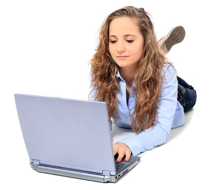 bonny: Attractive young girl lying on floor using notebook computer. All on white background.  Stock Photo