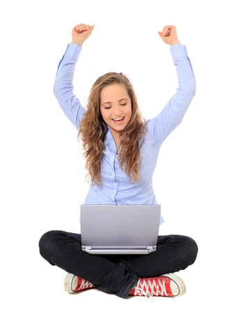 indian style sitting: Cheering young girl using notebook computer. All on white background.  Stock Photo