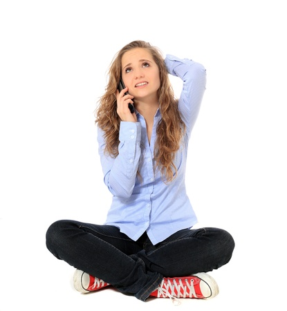 indian style sitting: Attractive young girl making a phone call. All on white background.  Stock Photo