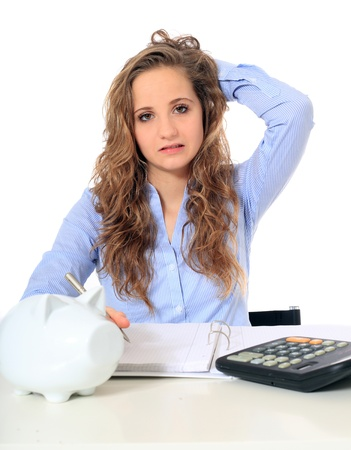 Portrait of a frustrated young girl doing her budgeting. All on white background.  photo