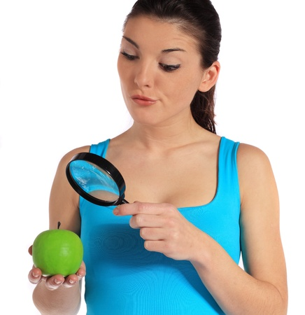 skeptic: Attractive young woman checking an apple through a lens. All on white background.