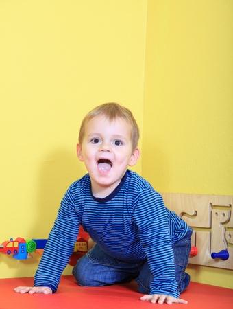 express positivity: Cute caucasian toddler having fun in kindergarten.  Stock Photo