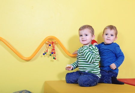 hermanos jugando: Lindos europeos ni�os en una guarder�a. Foto de archivo