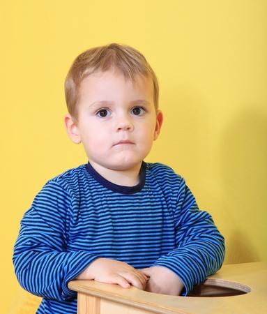 Cute caucasian toddler missing his mum in kindergarten.  photo