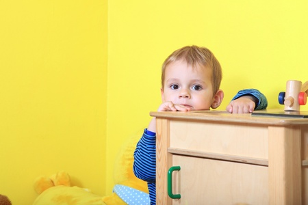 hide and seek: Cute european toddler playing hide and seek in kindergarten. Extra text space on left side.  Stock Photo