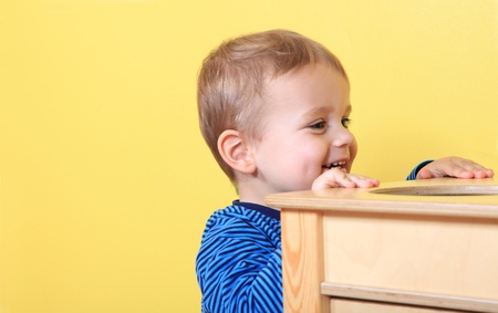 Cute european toddler having fun in kindergarten. Extra text space on left side.  photo