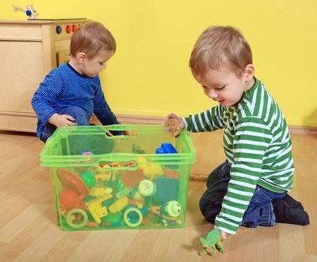 put away: Cute european toddlers in kindergarten.