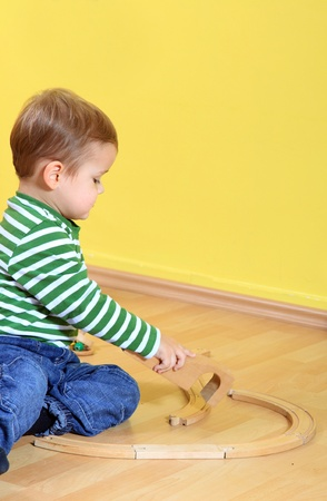Cute caucasian toddler playing with toy train in kindergarten. Extra text space on upper right corner.  photo